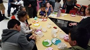 students and families working on marshmallow shapes
