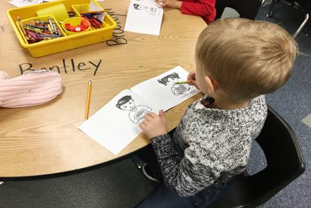 A kindergarten student uses his mini book to learn about healthy nutritious choices.