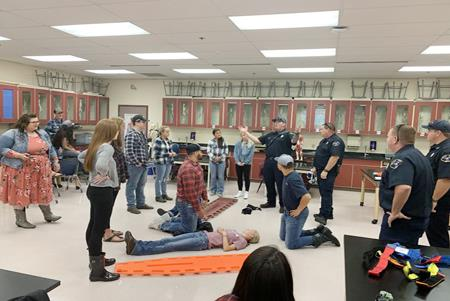Sports medicine students team with the Selah Fire Department to learn the correct spine board techniques.